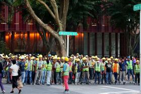 ALL SAFE: (above) Workers from the construction site were evacuated to a grass patch  along Wallich Street.
