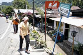 SAFE ZONE: Residents of Padang in western Sumatra walking near a sign that marks a tsunami evacuation route.