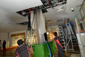CLEANING UP: A kitchen waste pipe in Shaw Foundation Alumni House burst, causing waste water to leak from the ceiling to the floor of the first storey. TNP PHOTOS: CHOO CHWEE HUA