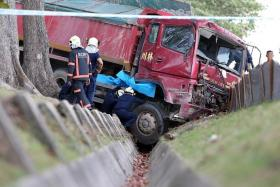 DEAD: Mr Zailee Othman was sitting by the roadside as his container truck had broken down when he was hit by a tipper truck, which ended in a ditch.