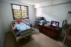 DEVOTED: Mr Ng Moh Hiong, 72, and his wife, Madam Lau Siew Lan, 69, take turns watching over their bedridden, 38-year-old daughter, Margaret.