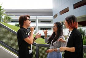 COMMUNICATION: Two of Brendan Lau's classmates at Millennia Institute, Miss Charisse Agustin (in grey) and Miss Lena Loke (in black), learnt sign language to help them communicate better with him.