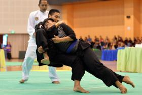 DOWN YOU GO: Seni Grasio's Alfian Juma'en executing a takedown on his opponent (with blue sash) at the National Championships at Pasir Ris Sports Hall yesterday.