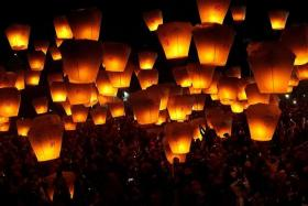 UPLIFTING: (Above) People release sky lanterns as a form of prayer for good luck and blessings. Some 200 lanterns were released each time at 15 minute intervals and a total of 1,600 were released that night.