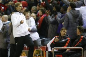 Liverpool manager Juergen Klopp celebrates after Roberto Firmino scored their second goal as Manchester United's bench (background) look on.