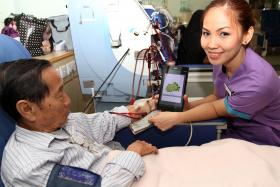 TRANSLATION HELP: NKF's healthcare assistant Junna Rae Estampador can now communicate better with her patient, Mr Lai Kim Leong.