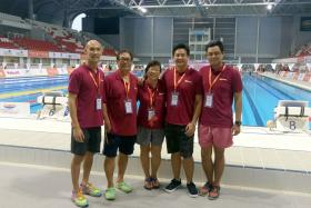 THE COACHES: Elsie Chiang (centre), along with Mark Chay (second from right) and some of the Aquarian Aquatic Swim School coaches at the end of the Singapore National Age- Group (Junior) Swimming Championships at the OCBC Aquatic Centre yesterday.