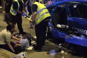 AFTERMATH: Two girls (above) were injured and attended to after their taxi was hit by a lorry on Sunday along Jurong East Street 21.