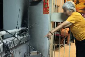 CHARRED: Rescue officers extinguishing the fire. (Above) Madam Lum pointing to the damage her son did. Photos: shin Min Daily news