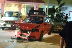 DAMAGE: After crashing into a red car, the ComfortDelGro taxi reversed into the void deck of Block 702, Bedok Reservoir Road, on Thursday night. The red car was badly damaged (above).
