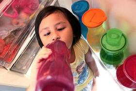 FEELING THE HEAT: Five-year-old Aisyah Zahra drinking cold water to while standing in front of the refrigerator.