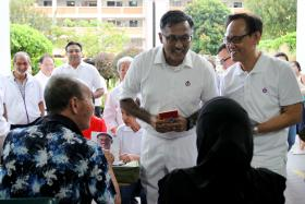 HEAD TO HEAD: (Above) PAP candidate K. Muralidharan Pillai with Bukit Batok residents yesterday. SDP candidate Chee Soon Juan during a walkabout in Bukit Batok on March 13.
