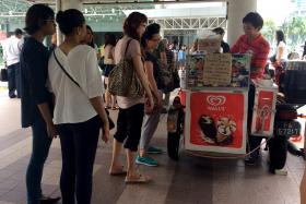 HIS TREAT: Customers queueing for Mr Jimmy Teng's free ice cream outside Lavender MRT station.