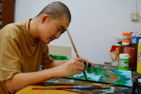 ARTWORK: Volunteers from A Packet Of Rice helped Mr Low Mun Chong ( above ) sell his paintings.
