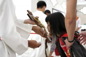 RESPECT: (Above) The Veneration of the Cross. Christians honour the cross by kneeling before it and kissing it.