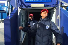 LESSON LEARNT: Singaporean teenagers Nuruddin Irsyad Samion (left) and Effan Putra Ibrahim stepping out to the pitch at QPR's Loftus Road home ground. (Inset) The poster in the QPR canteen with a message that made a strong impression on the boys.