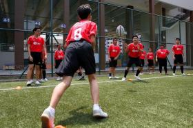 ONE STEP AT A TIME: The students going through a passing drill as they learn the basics of rugby.