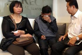 GRIEF: (Above) Undertaker Roland Tay (far right) speaking to Miss Zhang's parents.