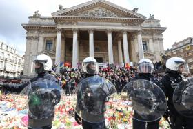 WarY: Riot police surrounding the makeshift memorial in tribute to the victims of the Brussels terror attacks last week.