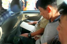 CHARGED: Boh Soon Ho arriving at the State Courts yesterday accompanied by police officers.