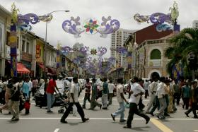 CROWDED: Foreign workers crossing Serangoon Road in Little India.