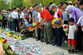 Prime Minister Lee Hsien Loong (in red shirt) and his wife Ho Ching putting flowers at the Garden of Remembrance on March 19 to mark the first anniversary of the passing of Mr Lee Kuan Yew.
