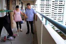 FOLLOW ME: Mr Suhaime Roa teaching Madam Siti Hajar Abdul Gaffar how to navigate the corridor outside her flat with a walking cane.