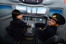 SKY'S THE LIMIT: Children 'fly' an airplane in a flight simulator.