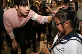 BIG HEART: Student Lim Qi Hui (right) was shoved to the ground when fans pushed forward to shake hands with Korean actor Park Hae Jin (in pink), and was helped up and comforted by him.