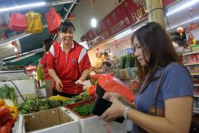 FAMOUS: Everyone at Jurong West knows vegetable seller Beh Poh Gek (in red shirt) for her friendliness and loud voice.