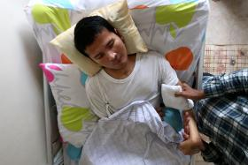 CONSTANT CARE: (Above) Mr Yuri Dahlan Ismail is bedridden and unable to communicate.