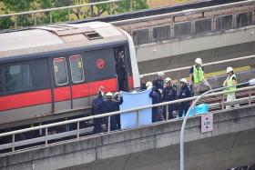 ACCIDENT: Singapore Civil Defence Force officers recovering the bodies of Mr Nasrulhudin Najumudin and Mr Muhammad Asyraf Ahmad Buhari near Pasir Ris MRT station on March 22. Mr Nasrulhudin and Mr Asyraf were undergoing training at SMRT when they died.