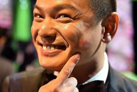 HAPPY: (Above) Chew showing off one of the lipstick marks he received at the Star Awards Show 2.