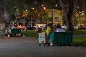 SEARCH: Dumpsters along an alley near Buffalo Road in Little India, a dumpster diver looking through unwanted vegetables at the wet market in Lorong 1, Toa Payoh, and another dumpster diver (above) rummaging through a dumpster outside the same wet market.