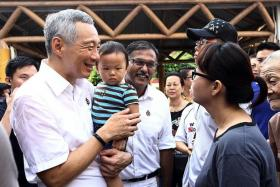 ALL SMILES: PM Lee Hsien Loong and PAP candidate for Bukit Batok by-election Murali Pillai greeting people around the estate during a walkabout