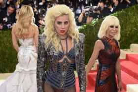 """Our Writer Wee Teck crowned Lady Gaga (centre) as the best dressed during the Metropolitan Museum of Art Costume Institute Gala (Met Gala). She is seen here posing with designer Donatella Versace (right) as they are arrive at the Met Gala to celebrate the opening of """"Manus x Machina: Fashion in an Age of Technology"""""""