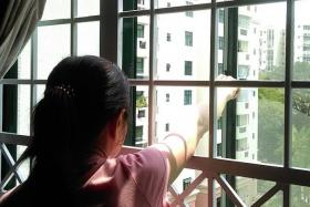 NEIGHBOUR: (Above) Mr Cheong's wife showing where Mr Timothy Ng stood before they opened the grilles of their sixth-floor unit.