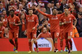 Liverpool's English striker Daniel Sturridge (2nd R) celebrates scoring his team's second goal during the UEFA Europa League semi-final second leg football match between Liverpool and Villarreal CF at Anfield.  His team qualifies for the Europa League final.