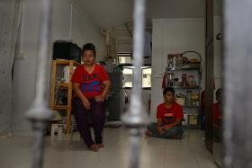 VICTIM: Madam Jurina with one of her two sons, Mr Muhammad Shahirul Junadi, who is autistic, in their one-room rental flat.