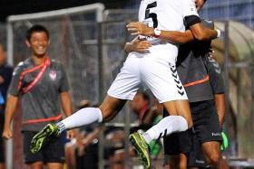 JUMP FOR JOY: Albirex's Naofumi Tanaka hugging a staff member after scoring their third goal.