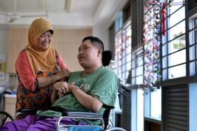 CARE: Madam Jamilah Othman's son Mr Khairul Abdul Majid is in a nursing home after getting into an accident 12 years ago.