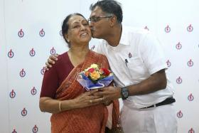 ELECTED: (Above) Mr Murali Pillai giving his mother, Madam Vasanthi Ramadass, a bouquet of flowers and a kiss after the press conference.