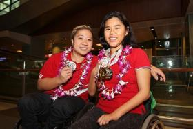 GLITTERING HAUL: Para-swimmers Theresa Goh (left) and Yip Pin Xiu with their medals won at the International Paralympics Committee Swimming European Open Championships. Goh claimed a bronze medal, while Yip won two golds and one silver.