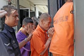 NABBED: A Singaporean monk (in orange) and his live-in female partner were arrested in Kulai, Johor Baru, for allegedly hitting their maid with a hammer after she rejected his attempts to marry her.