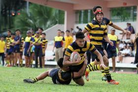VALIANT ATTEMPT: ACS (I)'s two-try scorer Edward Hui (holding ball) being tackled by an ACJC player en route to their 45-5 win yesterday.