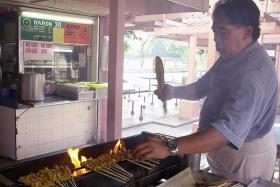 HAWKERS: (Above) Mr Haron Abu Bakar, founder of Haron Satay, has died. His daughter, Madam Harlina Haron, now runs the stall with her sister.