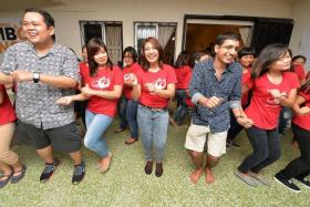 IN HARMONY: Mr Suraj Prakash Upadhiah (second from right) dancing with foreign domestic workers at a gathering at his home on May 7.