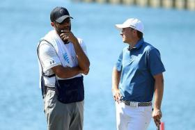 POOR SHOW: Spieth (right) cuts a dejected figure as he speaks to his caddie Michael Greller.
