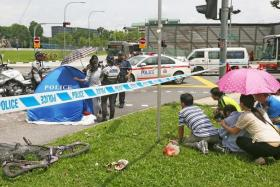 TRAGIC: Madam Lin's grief-stricken family members being restrained at the scene of the accident in Yishun.