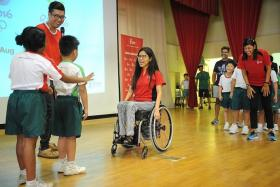 STAR POWER: Paralympic swimming champion Yip Pin Xiu (centre) and national floorball team goalkeeper Fariza Begum (far right) were enthusiastically received by Zhonghua Primary School pupils (in white and green).